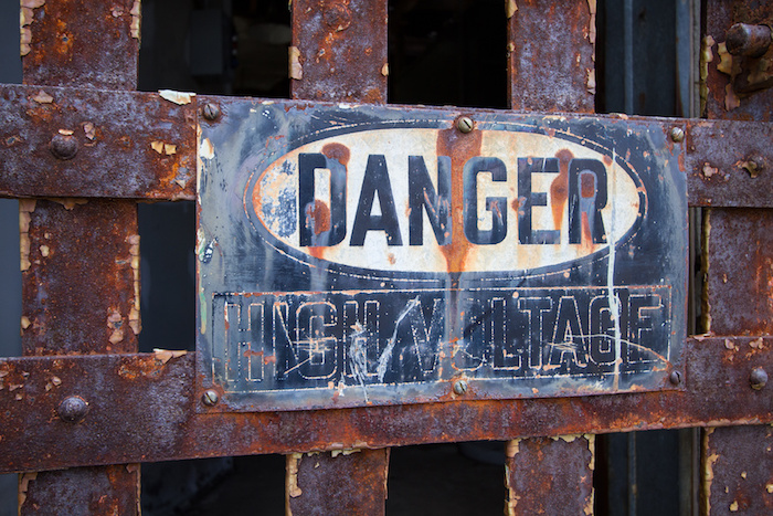 A sign on a construction site warning workers of the high voltage in the area
