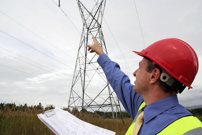 A construction supervisor pointing out power lines and wires before using a mobile crane